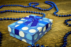Beautiful blue a present with blue beads on a wooden background.  Royalty Free Stock Image