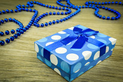 Beautiful blue a present with blue beads on a wooden background.  Stock Images