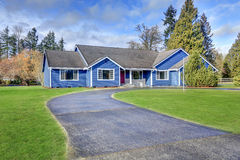 Beautiful blue rambler house with tile roof Stock Photos