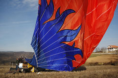 Beautiful Blue Red Hot Air Balloon Deflating on Ground Stock Photo