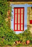 Beautiful blue and red window in mediterranean village house Stock Images