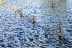 Beautiful Blue Rippling Waters with Wooden Fence Post. Wooden Fence Post and plastic net reflected in the water stock image