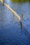 Beautiful Blue Rippling Waters with Wooden Fence Post. Wooden Fence Post and plastic net reflected in the water royalty free stock photography