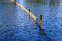 Beautiful Blue Rippling Waters with Wooden Fence Post. Wooden Fence Post and plastic net reflected in the water stock photo