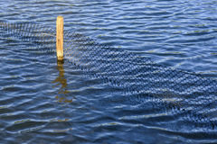 Beautiful Blue Rippling Waters with Wooden Fence Post. Wooden Fence Post and plastic net reflected in the water royalty free stock image