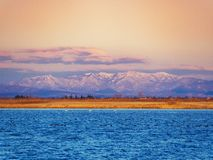 Beautiful blue salt lake with swans and black ducks. In it and awesome mountains far away on the horizon royalty free stock images