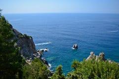 Beautiful rocky beach and some motorboats in Paleokastritsa, Greece. Beautiful blue sea and motorboats on the water nearby the coast of Paleokastritsa, Corfu Stock Photos