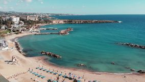 Beautiful blue sea with sandy beach. Aerial view of umbrellas and sunbeds. Drone shot of beach with white sand. Blue crystal clear stock video