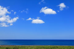 Beautiful blue sea, sky, green grass and cloud royalty free stock photography