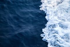 Blue Seawater with sea foam as background. Beautiful Blue Seawater with sea foam as background. Waves from a floating ship stock photo