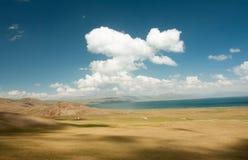 Beautiful blue sky with clouds over deep mountain lake Stock Photos