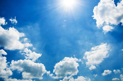 Beautiful blue sky, full of fluffy clouds. And a glowing sun Stock Photos
