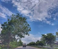 On The road from Nongkhai to Khonkaen, Thailand. Beautiful blue sky and green scenery along the side of the road from Nongkhai, Udon and Khonkaen, Thailand Royalty Free Stock Photo