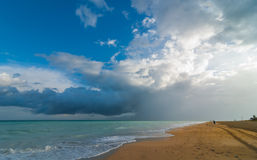 Beautiful blue sky holiday beach scene - getaway on a vacation beach in Cuba. Warm ocean waves gently lap against a Cuban beach.  Cloudscape on open beach with Stock Images