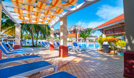 Beautiful blue sky holiday in Cuba.  View from pool,  getaway vacation in Varadero. Lay back on deck chairs.  Families and people relaxing on holidays Royalty Free Stock Photo