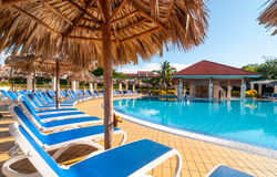 Beautiful blue sky holiday in Cuba.  View from pool,  getaway vacation in Varadero. Lay back on deck chairs.  Families and people relaxing on holidays Royalty Free Stock Photos