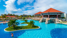 Beautiful blue sky holiday in Cuba.  View from pool,  getaway vacation in Varadero. Lay back on deck chairs.  Families and people relaxing on holidays Royalty Free Stock Image
