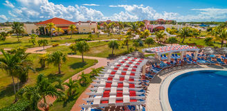 Beautiful blue sky holiday in Cuba.  View from pool,  getaway vacation in Varadero. Lay back on deck chairs.  Families and people relaxing on holidays Royalty Free Stock Photography