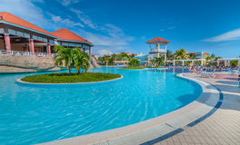 Beautiful blue sky holiday in Cuba.  View from pool,  getaway vacation in Varadero. Lay back on deck chairs.  Families and people relaxing on holidays Stock Photography