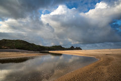 Beautiful blue sky morning landscape over sandy Three Cliffs Bay Royalty Free Stock Images
