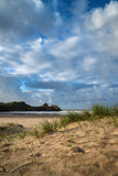 Beautiful blue sky morning landscape over sandy Three Cliffs Bay Stock Photo