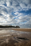 Beautiful blue sky morning landscape over sandy Three Cliffs Bay Royalty Free Stock Image