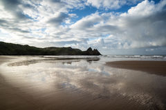 Beautiful blue sky morning landscape over sandy Three Cliffs Bay Stock Image