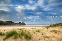 Beautiful blue sky morning landscape over sandy Three Cliffs Bay Royalty Free Stock Photos