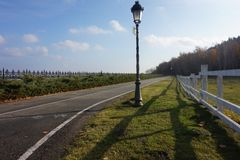An asphalt road to the forest. Near the lantern and fencing Stock Photo