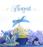 Beautiful blue Summer holiday theme cupcake with seasonal flowers and decorations for the month of August Stock Photo