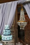 Beautiful blue three-tiered cake decorated with flowers on a stand, on the wedding table. Beautiful blue three-tiered cake on the table stock images