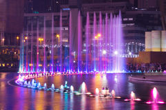 Beautiful blue and violet fountain in the night. Multicolor water streams in the dark Stock Photo