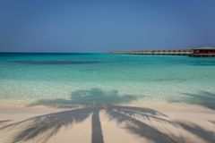 Beautiful blue water beach in a tropical paradise, with bungalows in the background in Maldives stock image