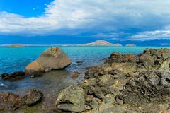 Beautiful blue water and rocks lake coast royalty free stock photos