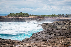 A beautiful blue wave crashes down at the rocks in Devil`s Tear, tropical island Nusa Lembongan, Indonesia, Asia. Sunny Stock Image
