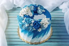 Beautiful blue wedding cake decorated with white flowers of cream. Concept of Holiday desserts for a birthday
