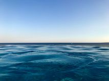 Beautiful blue wet azure natural clear water against a blue sky and horizon line in a tropical warm sea resort.  royalty free stock photo