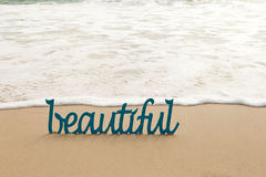Beautiful - blue wooden word in sand with waves on beach Royalty Free Stock Photo