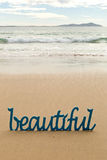 Beautiful - blue wooden word in sand with waves on beach royalty free stock photos