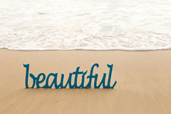 Beautiful - blue wooden word in sand with waves on beach stock photo