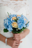 Beautiful blue and yellow fresh flowers wedding bouquet. Bride with wedding bouquet, closeup.  Stock Image