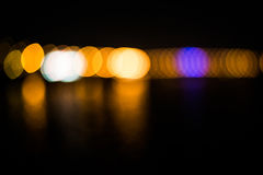 Beautiful blurred city lights with bokeh effect reflected on water background.  Royalty Free Stock Images