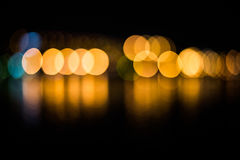 Beautiful blurred city lights with bokeh effect reflected on water background.  Stock Images