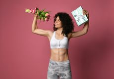 A beautiful body athletic girl with curly hair and in sportswear, holds in a strong muscular arm a bouquet of gentle tulpans stock images