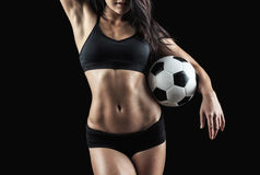 Beautiful body of fitness model holding soccer ball. Isolated on black background Royalty Free Stock Photography