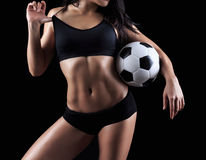 Beautiful body of fitness model holding soccer ball. Isolated on black background Royalty Free Stock Image