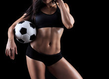 Beautiful body of fitness model holding soccer ball. Isolated on black background Stock Photography