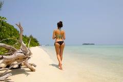 Beautiful body of girl in bikini walking back. At the beach Royalty Free Stock Image