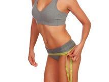Beautiful body girl measuring her waist Stock Photos