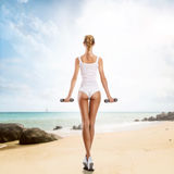 Beautiful body of young and woman working out on the beach royalty free stock photo